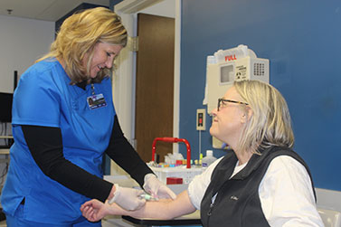 Nurse gives smiling patient a shot in the arm